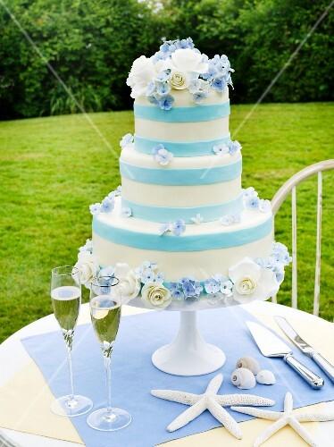 Dreistöckige blau-weisse Hochzeitstorte auf Tisch im Freien ...