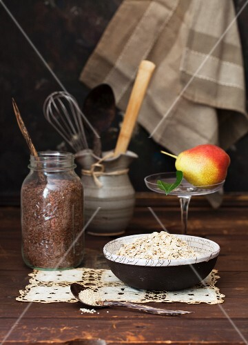 Oats, Flax Seeds and a Pear on a Rustic Wooden Table