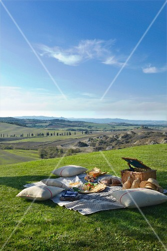 Picnic in meadow with view across Mediterranean, Tuscan landscape