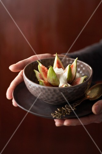 Hands holding a bowl of figs with cinnamon and mascarpone cream