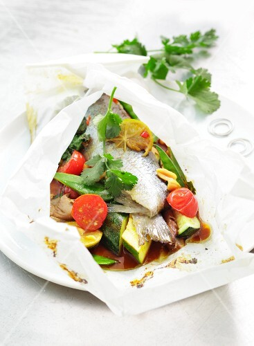 Trout in parchment paper with courgette, tomatoes and peanuts