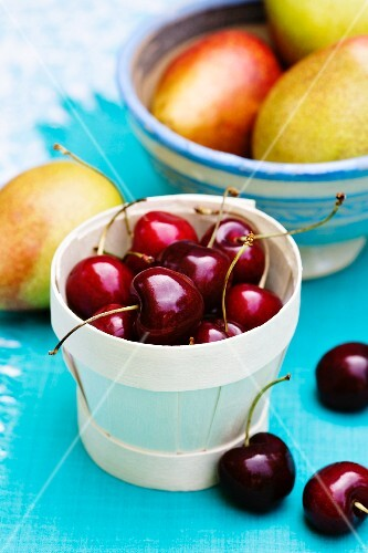 Cherries in a punnet in front of a bowl of pears