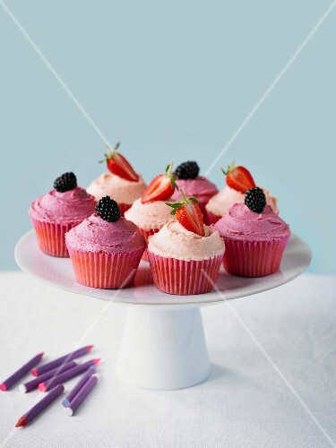 Cupcakes with strawberries and blackberries on a cake stand