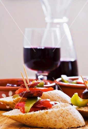 Pinchos with peppers and chorizo, served with red wine (Spain)