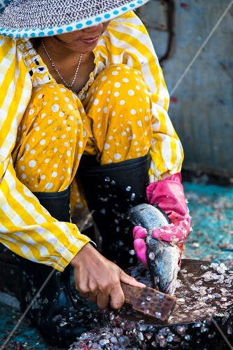 A woman scaling fish at a market in Phnom Penh, Cambodia