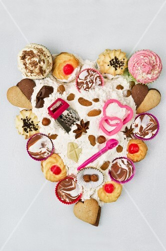 Cupcakes, biscuits, baking paraphernalia, chocolate and flour, arranged in a heart shape
