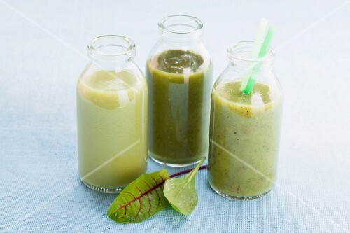Three green smoothies in glass bottles