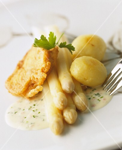 White asparagus with breaded fish fillet, potatoes and a herb sauce