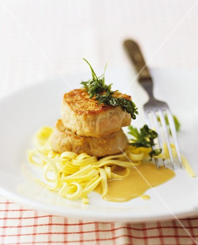 Pork medallions with a creamy sauce on ribbon pasta