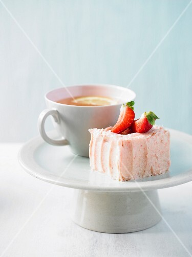 A cup of cake with strawberry buttercream, with a cup of tea