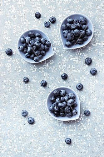 Blueberries in bowls on a patterned tablecloth (view from above)