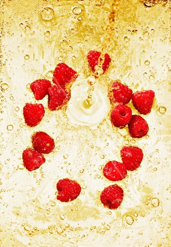 Sparkling wine being poured over raspberries