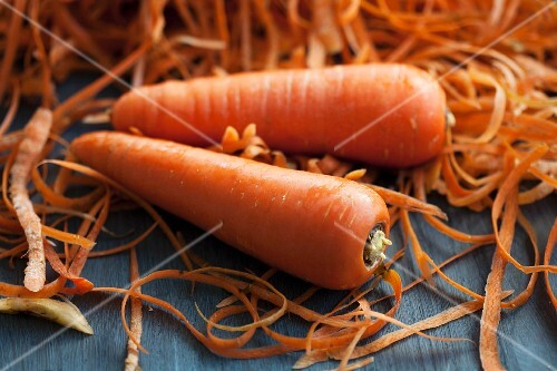 Two carrots next to a mound of carrot peelings