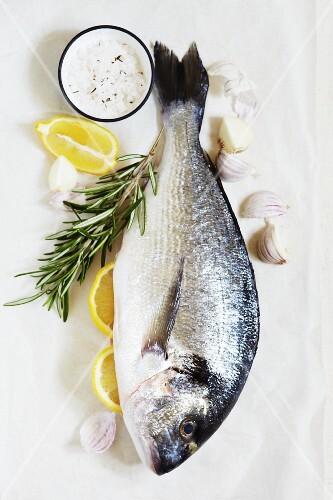 Gilt-head bream, garlic, lemon wedges and rosemary