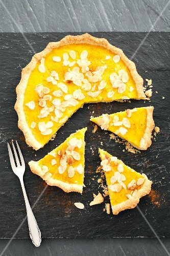 Pumpkin pie with cinnamon and sliced almonds, partly sliced