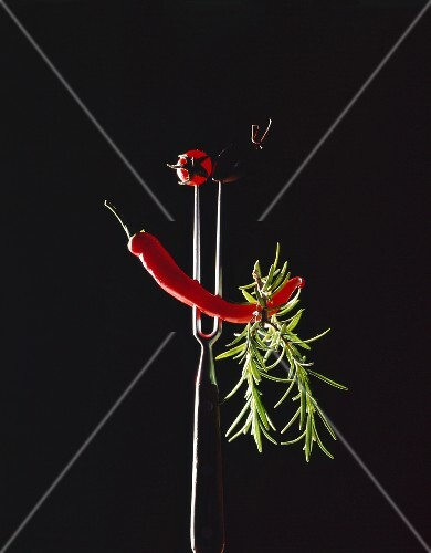 A chilli, a sprig of rosemary, a tomato and an olive skewered on a meat fork