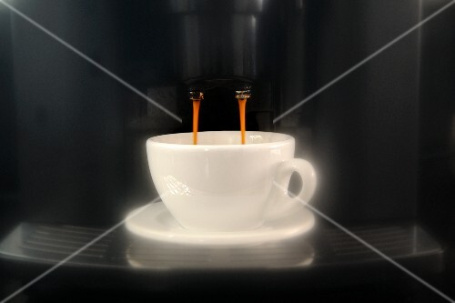 Coffee dripping out of an espresso machine into the cup