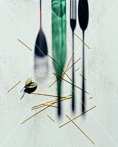 Scattered spaghetti next to a silhouette of a wine bottle, a glass and cutlery