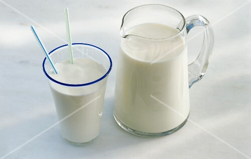 A jug of milk and a glass of milk with two drinking straws