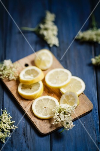 Lemon slices and elderflowers on a small wooden board