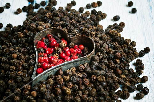 Red and black peppercorns with a cutter