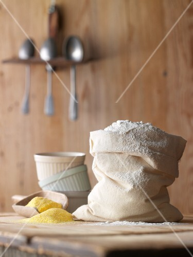 A bag of flour, polenta and baking moulds on a wooden table