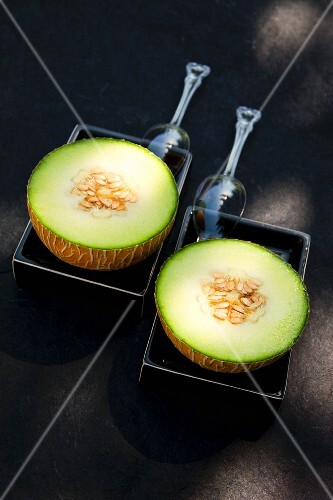 Two Galia melon halves in black ceramic dishes with plastic spoons