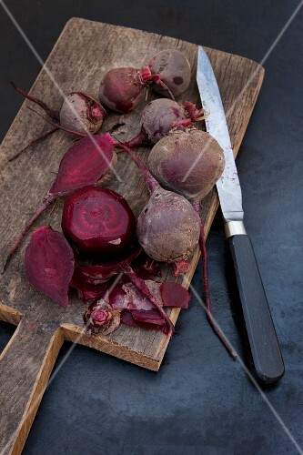 Several boiled beetroot, some peeled, on a wooden board with a knife