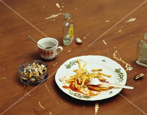 The remains of chips and ketchup on a plate, an ashtray, coffee and schnapps