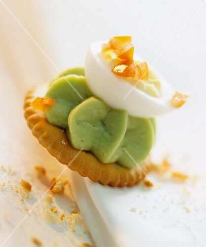 Cracker topped with avocado mousse and egg