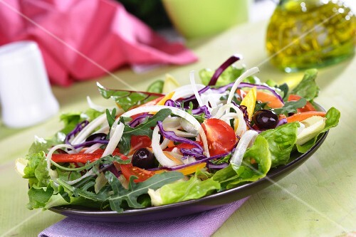Mixed salad leaves with sliced vegetables, tomatoes and olives