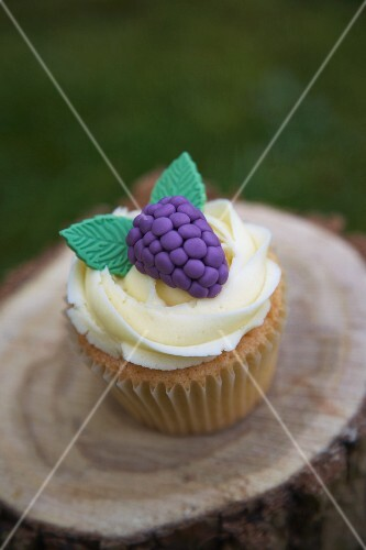 Blackberry cupcake on a tree stump