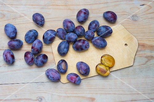 Fresh plums on a chopping board and on a wooden surface