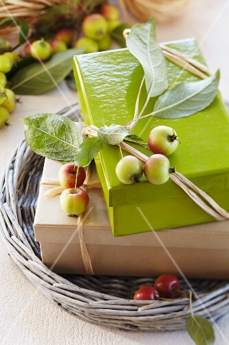Gift boxes on wicker tray tied with raffia ribbons and decorated with ornamental apples
