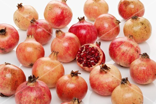 Lots of pomegranates, one halved