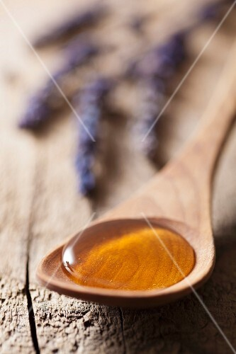 Honey on a wooden spoon, with lavender flowers in the background