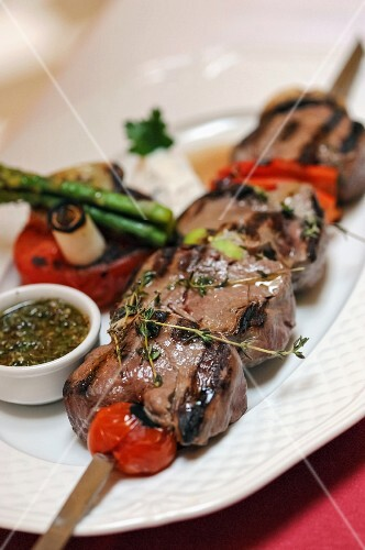 A barbecued pork skewer with tomatoes and thyme