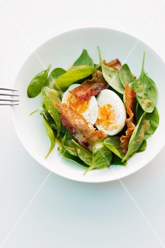 Spinach salad with bacon and a boiled egg