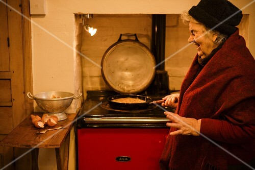 Elderly woman cooking Spanish omelette (tortilla)