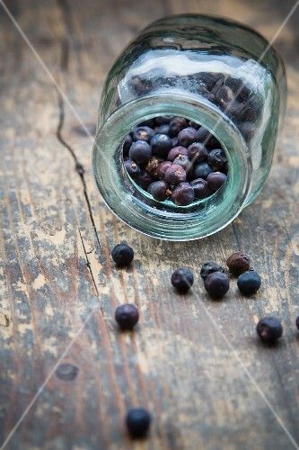 Juniper berries in an overturned jar on a wooden table