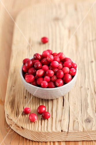 Cranberries in a small bowl on a chopping board