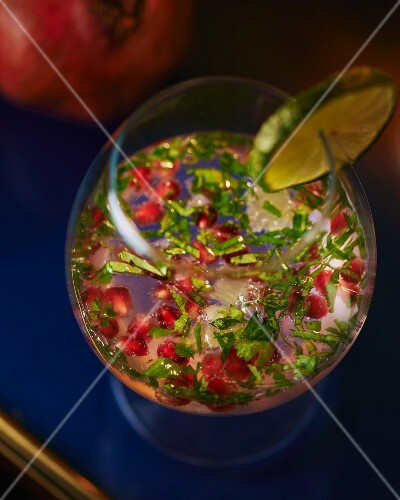 Pomegranate drink with vodka, herbs and lime