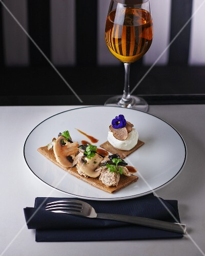 Mushroom pancake with mozzarella, truffle slices and a pansy