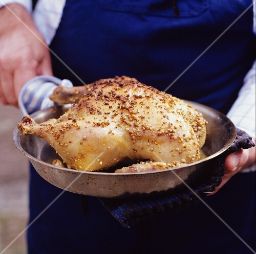 A person holding a pan with a crispy roast chicken