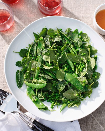 Plates of salad with peas and baby spinach