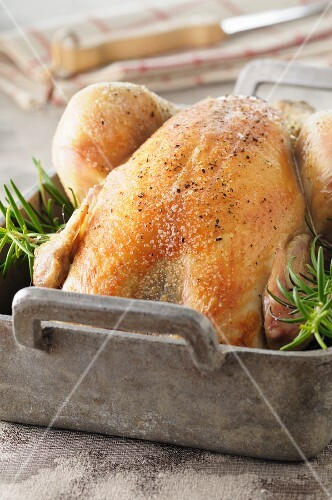 Roast chicken with rosemary in a roasting tin