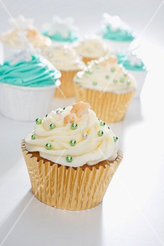 Cupcakes decorated with yellow and green icing and silver balls