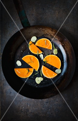Slices of raw butternut squash with garlic and rosemary in an old frying pan