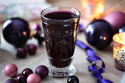 Mulled wine in a glass surrounded by Christmas tree baubles