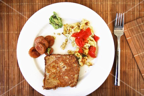 Scrambled egg with tomatoes, sausage and French toast, on a white plate